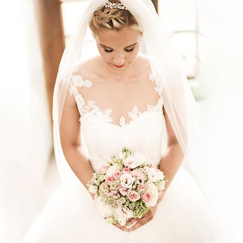 Hochzeitsfotograf Dresden - sinnliche Hochzeitsfotografie im Bouquet - Eine Braut schaut mit gesenktem Kopf auf ihren Brautstrauß.