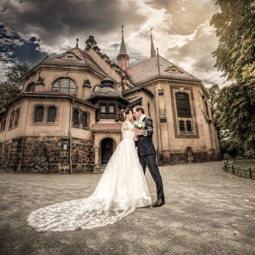 Hochzeitsfotograf Dresden - Ein romantisches Foto von einem Brautpaar vor einer Kirche.