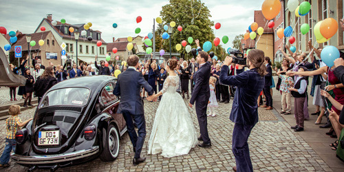 Hochzeitsfotograf Dresden - Die Hochzeitsgäste begrüßen das eintreffende Brautpaar mit bunten Luftballons.