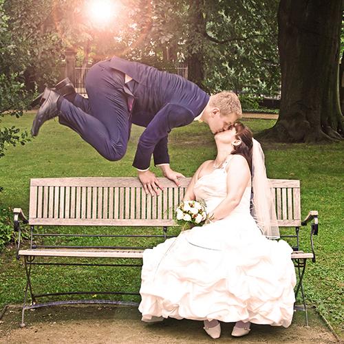 Hochzeitsfotograf Dresden - Ein Bräutigam springt über eine Bank und küsst dabei seine Braut. Die Sonne scheint durch die Äste der Bäume im Hintergrund.
