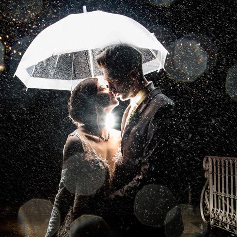 Hochzeitsfotograf Dresden - Ein Brautpaar steht im Regen unter einem Schirm mit Hintergrundlicht.