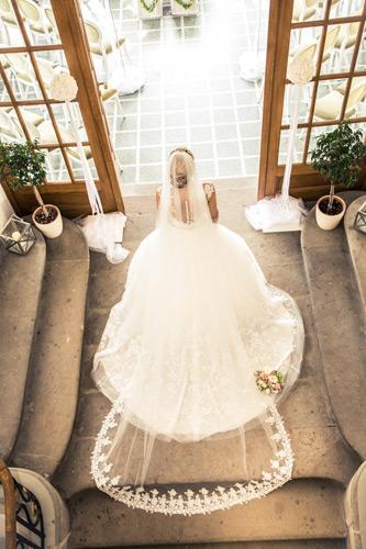 Hochzeitsfotograf Dresden - Eine Braut im Treppenhaus vom Weingut Proschwitz mit beeindruckendem Schleier.