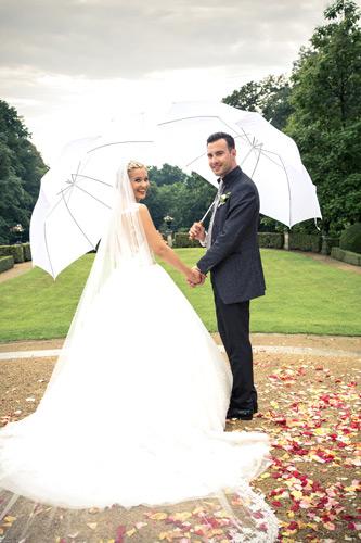 Hochzeitsfotograf Dresden - Das Brautpaar mit Regenschirmen in der Hand, hoffen auf besseres Wetter.