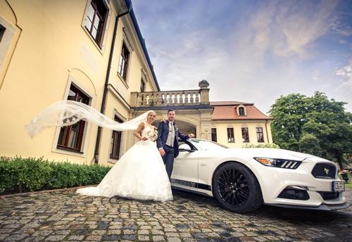 Hochzeitsfotograf Dresden - Das Brautpaar am Mustang vor dem Weingut Proschwitz bei Meißen. Die Braut hat einen wehenden Schleier.
