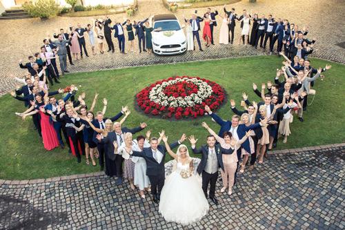 Hochzeitsfotograf Dresden - Eine glückliche Hochzeitsgesellschaft in Herzform von oben fotografiert.