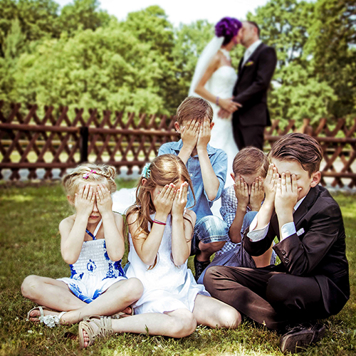 Hochzeitsfotograf Dresden - Das Brautpaar küsst sich und die Kinder halten sich die Augen zu.